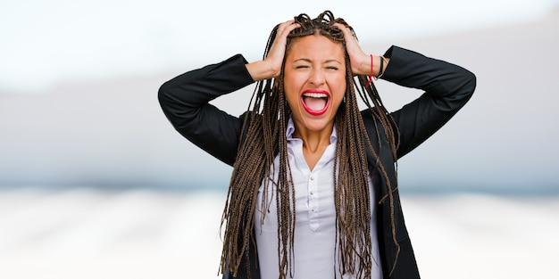 Portret van een jonge zwarte zakenvrouw gek en wanhopig, schreeuwen uit de hand