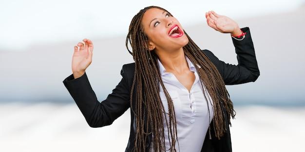 Portret van een jonge zwarte zakenvrouw luisteren naar muziek