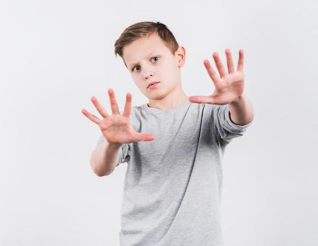 Portret van een jongen die aan camera kijkt die eindegebaar maakt die op witte achtergrond wordt geïsoleerd