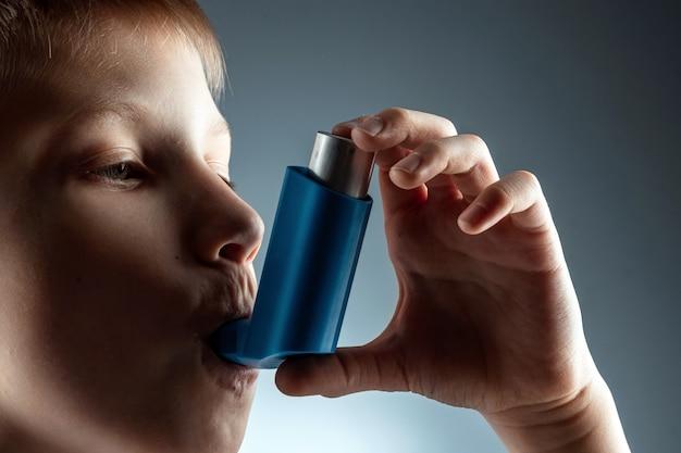 Portret van een jongen die een astma-inhalator gebruikt om ontstekingsziekten, kortademigheid te behandelen. het concept van behandeling voor hoest, allergieën, aandoeningen van de luchtwegen.