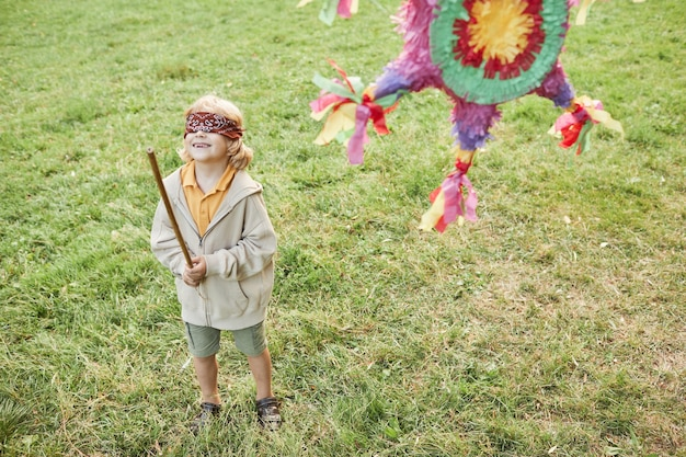 Portret van een jongen die een pinata-spel speelt op een verjaardagsfeestje in de buitenlucht en een kopie van de vleermuis vasthoudt