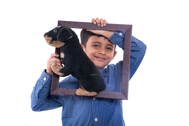 Portret van een jongen die gevuld stuk speelgoed huisdier met frame op een witte muur houdt