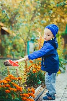 Portret van een jongen die in de tuin werkt
