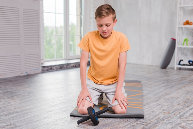 Portret van een jongen die op oefeningsmat knielt die roldia bekijkt