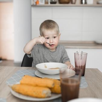 Portret van een jongen die voedsel thuis eet