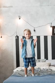 Portret van een jongen die zich op bed met verlicht licht op muur bevindt