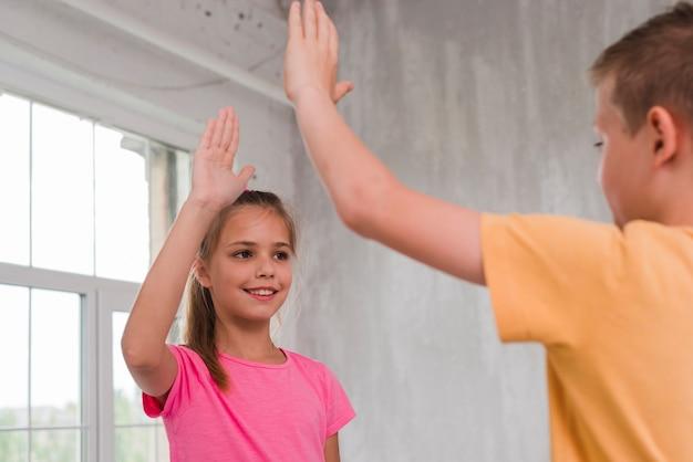 Portret van een jongen en een meisje die hoogte vijf geven