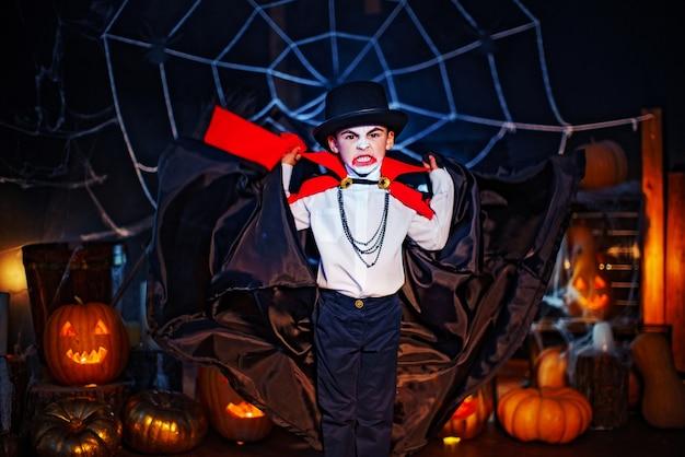 Portret van een jongen gekleed in een kostuum van een vampier en hoed over grungeachtergrond. halloween feest.