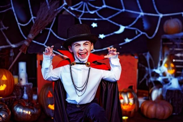 Portret van een jongen gekleed in een kostuum van een vampier over grungeachtergrond. halloween feest.