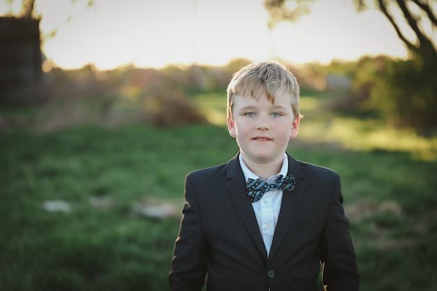 Portret van een jongen gekleed in een pak met blauwe strik