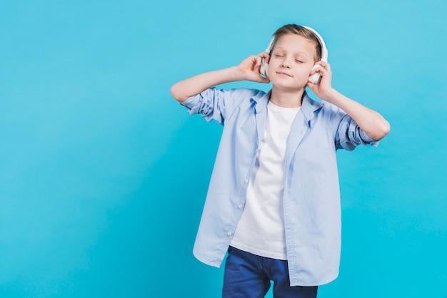 Portret van een jongen het luisteren muziek op witte hoofdtelefoon tegen blauwe achtergrond