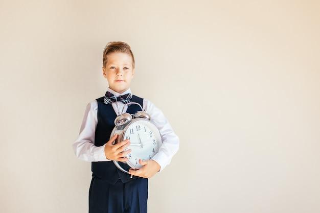 Portret van een jongen in grijs pak met grote klok. leuke jongen die grote klok houdt. kind terug naar school, op neutrale achtergrond. onderwijs en tijd concept.