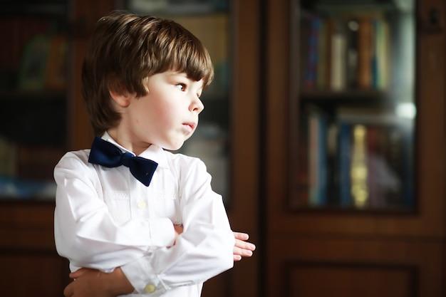Portret van een jongen met bruine ogen in een overhemd en een zwarte vlinderdas op een donkere achtergrond. het kind is emotioneel, lacht, heeft plezier, is gelukkig.