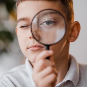 Portret van een jongen met een vergrootglas in de klas