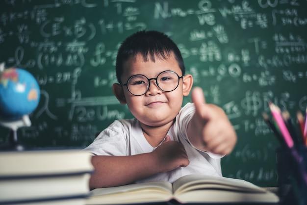 Portret van een jongen met handenduimen omhoog in het klaslokaal.