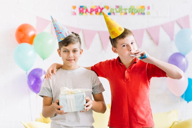 Portret van een jongen met zijn vriend verjaardag cadeau te houden
