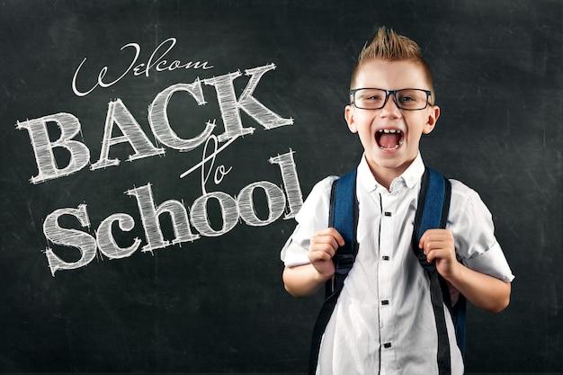 Portret van een jongen uit een basisschool met de tekst terug naar school op een schoolbord