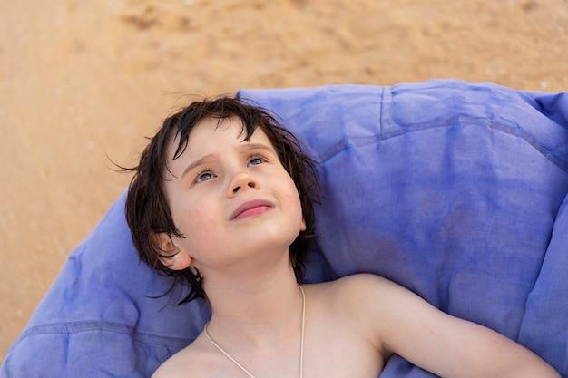 Portret van een jongen zittend op een zitzak stoel op het strand van het resort in de zomer. kind dat omhoog in de lucht kijkt.