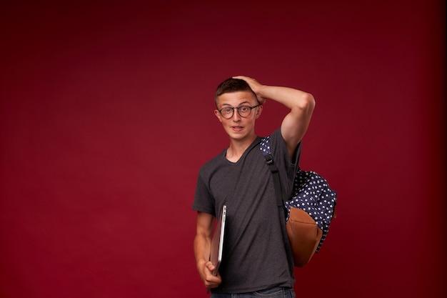 Portret van een jongensstudent die met een rugzak en laptop in zijn handen op rood glimlachen