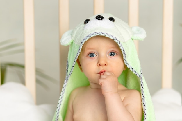 Portret van een jongetje in een groene handdoek na een bad op het bed thuis met een vinger in zijn mond