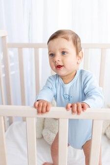 Portret van een jongetje in een wieg in een kinderkamer met grote blauwe ogen