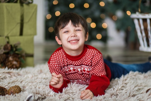 Portret van een jongetje spelen met dennenappels in de buurt van een kerstboom, kerstversiering, vrolijk kerstfeest en gelukkig nieuwjaar 2020,