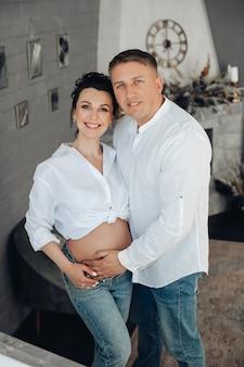 Portret van een joviaal, openhartig kaukasisch koppel in witte overhemden en spijkerbroeken die naar de camera glimlachen in een eigentijds interieur. zwangere vrouw met echtgenoot.
