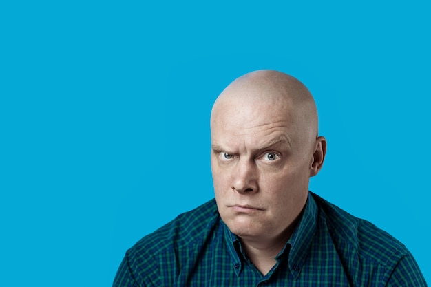 Portret van een kale brutale man in een plaidoverhemd op een blauw