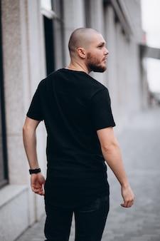 Portret van een kale knappe bebaarde man in een zwart t-shirt op straat, die weg kijkt