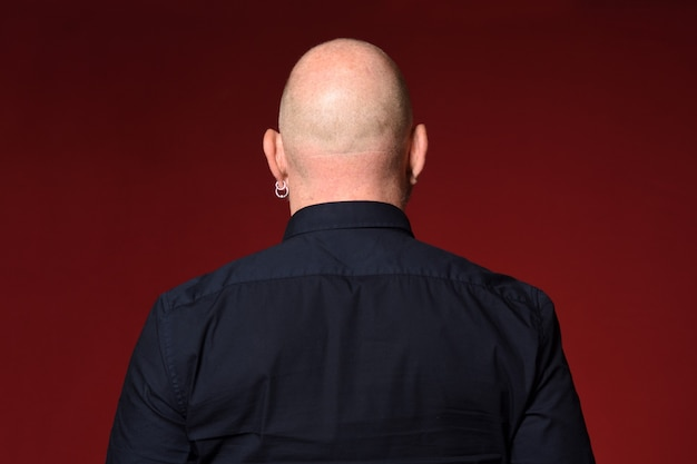 Portret van een kale man, achteraanzicht, op rode achtergrond