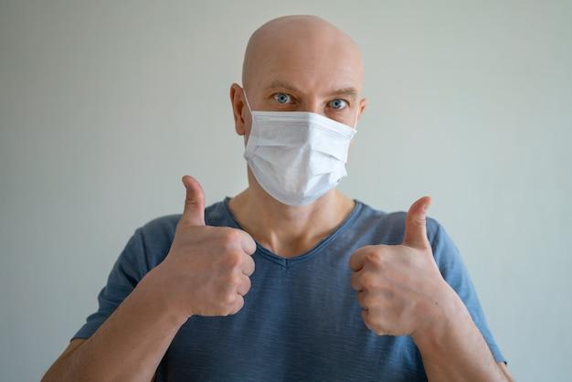 Portret van een kale man in een medisch masker, toont een handgebaar als een vinger omhoog