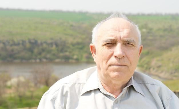 Portret van een kalende grijze haren senior man in de zomerzon met een vallei en een meer op de achtergrond