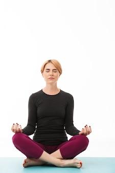 Portret van een kalme yogavrouw die in lotusbloem mediteert