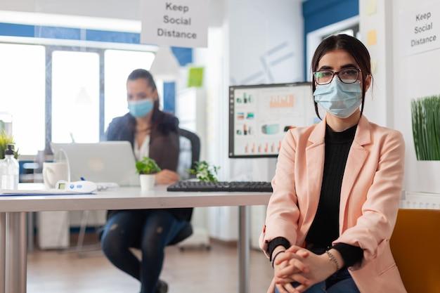 Portret van een kantoormedewerker die een gezichtsmasker draagt als veiligheidsmaatregel tijdens de wereldwijde pandemie met coronavirus die naar de camera kijkt en sociale afstand houdt. manager die aan laptop met plastic shi . werkt