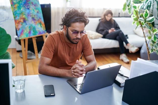 Portret van een kantoormedewerker die een laptop en mobiele telefoon gebruikt in een comfortabele en moderne kantoorruimte. indiase man werkt thuis.