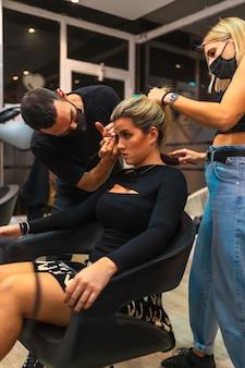 Portret van een kapper en een make-up artist in medische maskers die hun baan nieuw normaal doen
