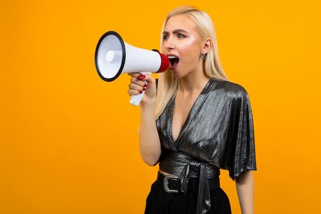 Portret van een kaukasisch blond meisje in een grafietblouse die nieuws in een megafoon op een gele studioachtergrond spreekt