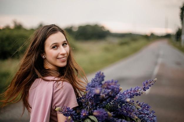 Portret van een kaukasisch, mooi brunette meisje dat oprecht lacht en op de weg in de voorsteden staat met een groot boeket wilde violette lupines