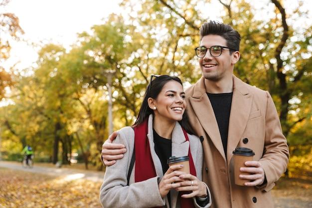 Portret van een kaukasisch stel, man en vrouw van 20 jaar die afhaalkoffie drinken uit papieren bekers tijdens het wandelen in het herfstpark