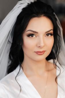 Portret van een kaukasische brunette van de meisjesbruid met make-up en styling op de ochtend van de huwelijksdag