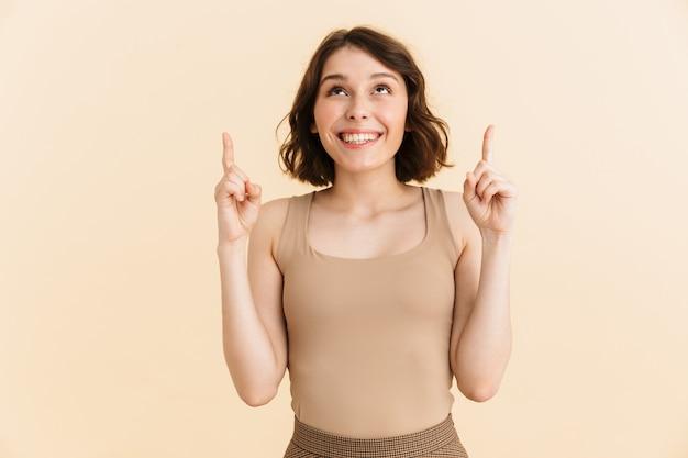 Portret van een kaukasische, vrolijke vrouw uit de twintig, gekleed in vrijetijdskleding, glimlachend terwijl ze met de vingers naar geïsoleerde copyspace wijst