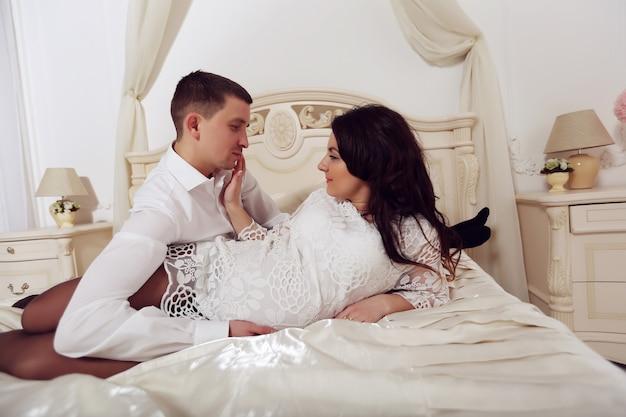 Portret van een kaukasische zwangere babyschoenen van de vrouwenholding en van haar echtgenoot op een bank thuis