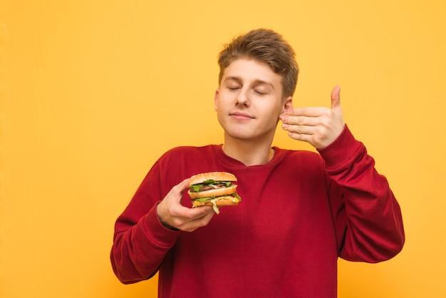 Portret van een kerel die een hamburger in zijn handen houdt en genietend van zijn gesloten ogen