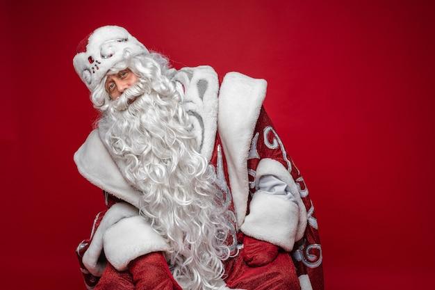 Portret van een kerstman met witte baard en lange witte baard in traditioneel buitensporig kostuum dat naar rechts leunt.