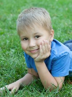 Portret van een kind dat op het gras ligt
