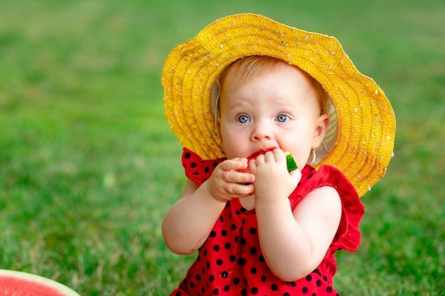 Portret van een kind in de zomer op het groene gras dat een watermeloen eet in een gele hoed, ruimte voor tekst