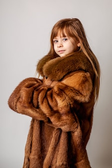 Portret van een kind in een domme bui. poserend in een grote natuurlijke jas met een bontkraag.