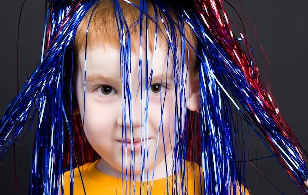 Portret van een kind met rood haar, een mooie jongen die voor de camera poseert, kinderen van 6-7 jaar, een close-up van een jongensmodel