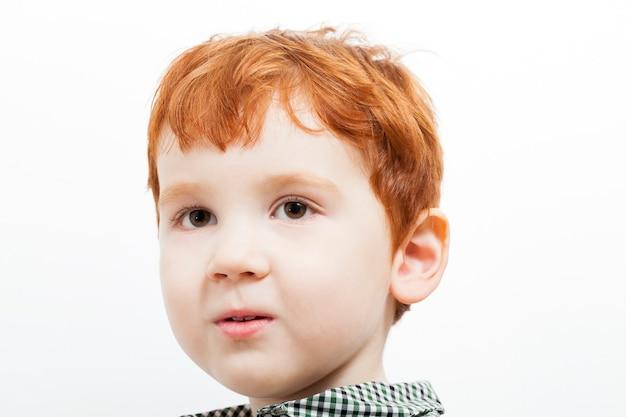 Portret van een kind met rood haar en sproeten op zijn gezicht, bruine ogen, op een lichte achtergrond