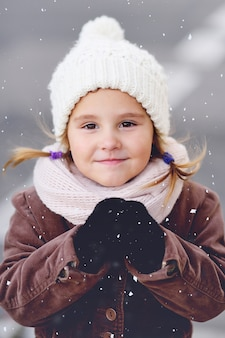 Portret van een kind van een klein meisje in een witte warme muts en in een sjaal